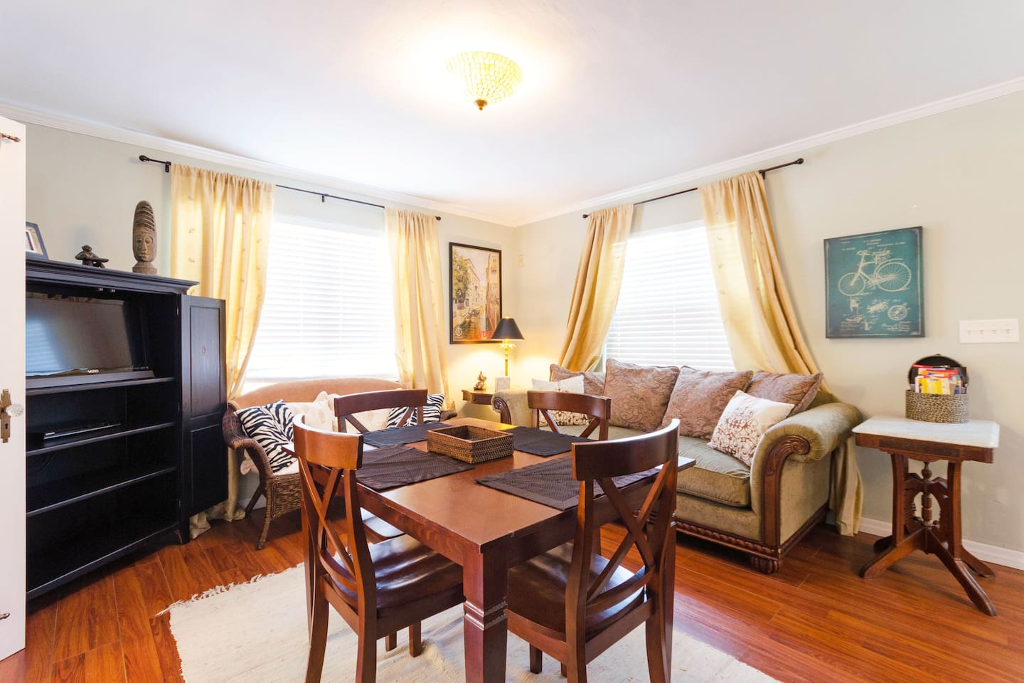 Livingroom with plush, overstuffed couch, wicker loveseat, dining table for four, flat screen T.V. with cable and DVD player