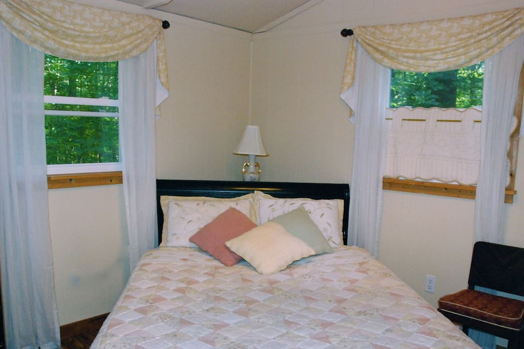 Queen-sized bed, flanked by 2 windows, enjoys wooded views through the sliding glass door.