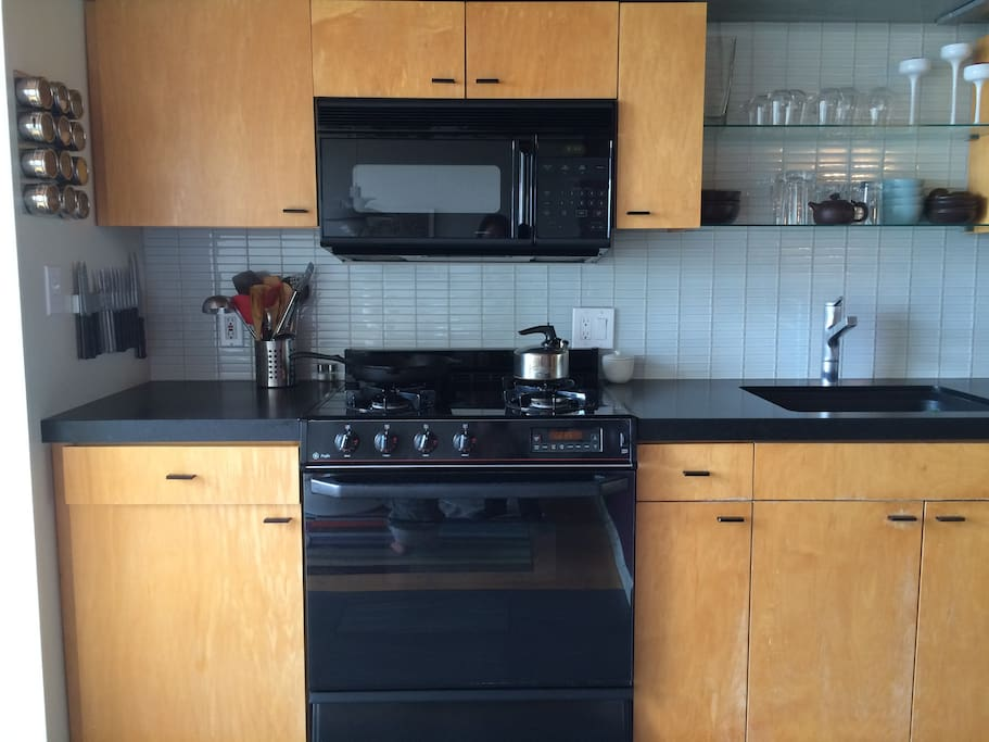 There is a black leather honed granite countertop and glass backsplash tiles.