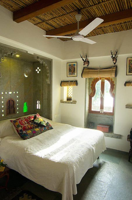 The luxurious bedroom with the beautiful bamboo ceiling and 1950's papiermache spotted deer 'trophies' above the window.