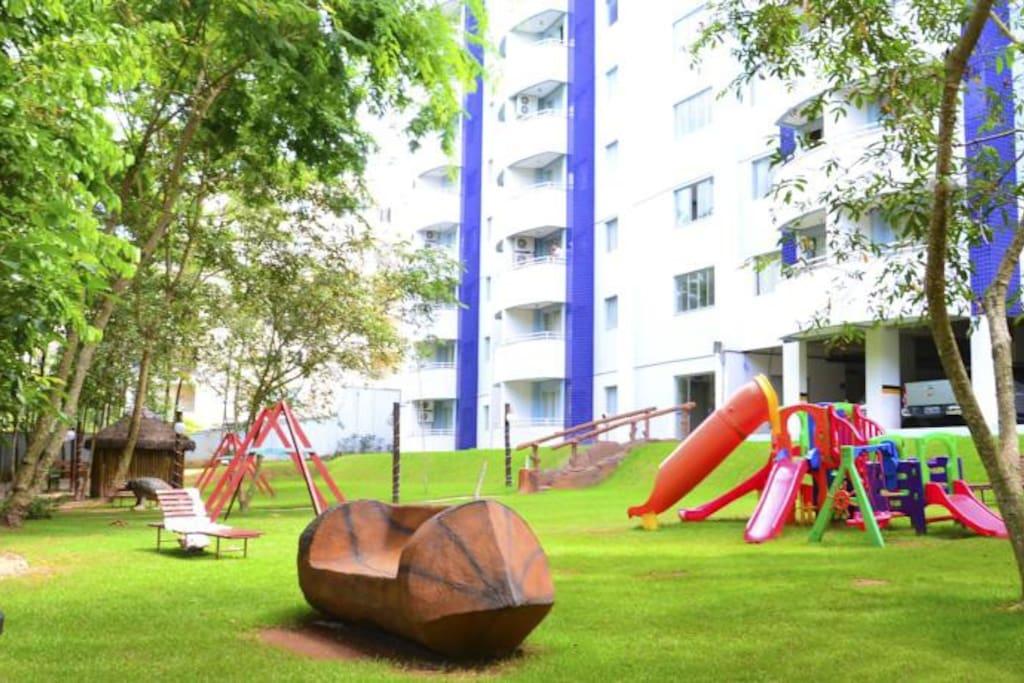 Área verde com alguns brinquedos para crianças.