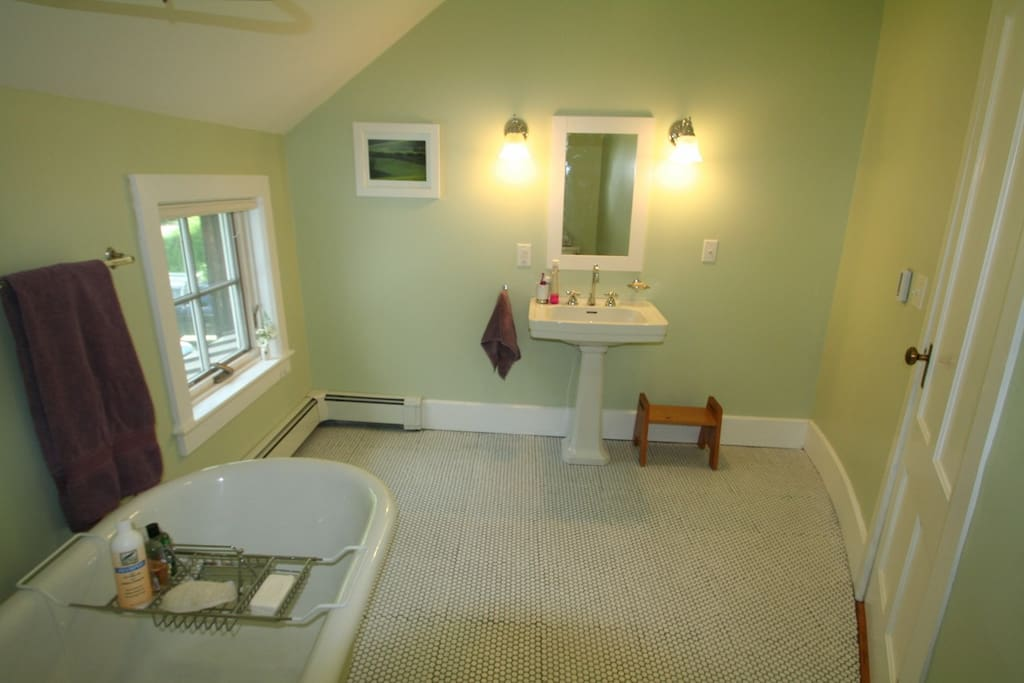 The bathroom with claw foot tub and heated tile floor.