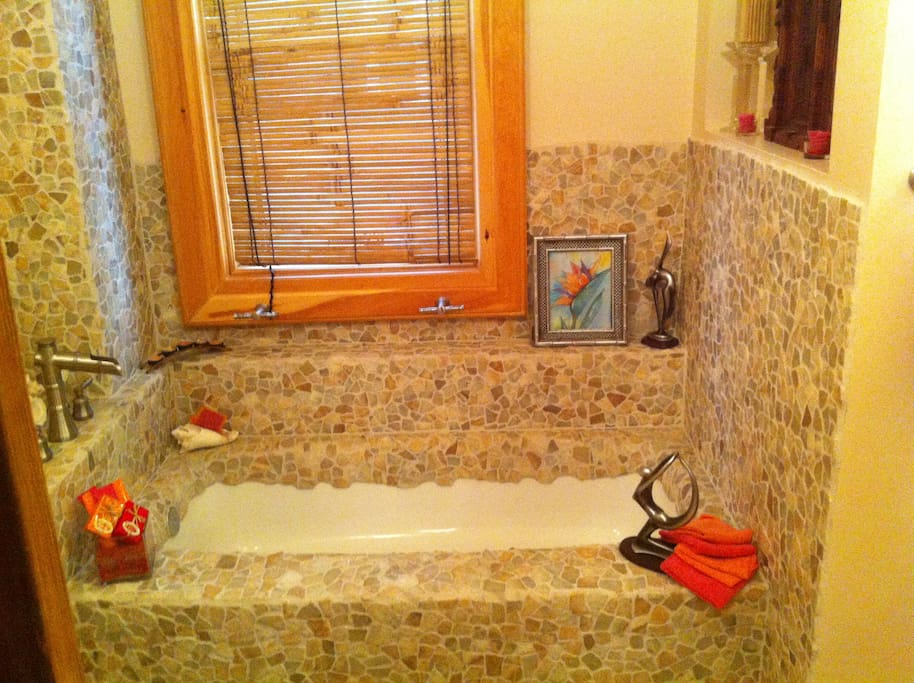 Hand-laid Balinese river stone around bath and sink. Yoga-theme accessories.