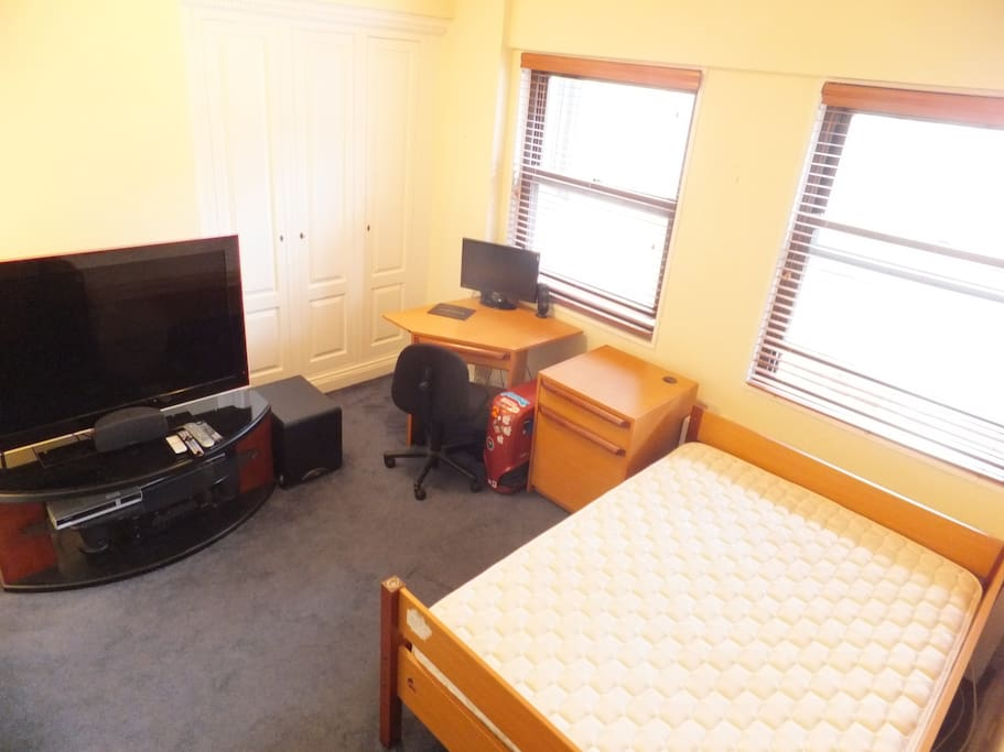 Bedroom has full-size firm mattress, ample built-in closet space and drawers, desk and chair and flat screen TV (no longer the large one in photo)