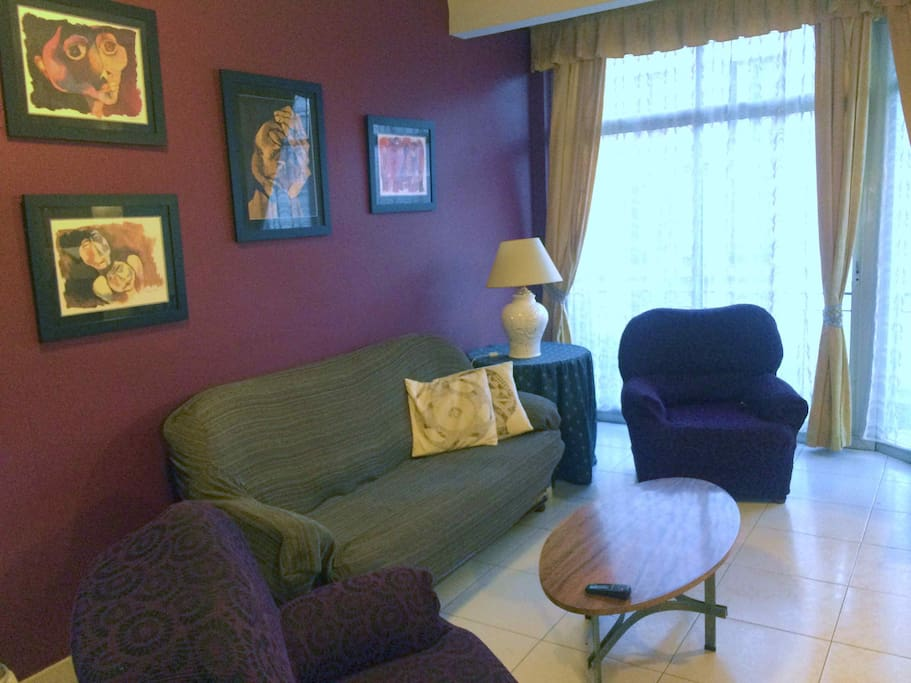 Big, comfortable living room with 3-seat couch, two armchairs and air conditioning
