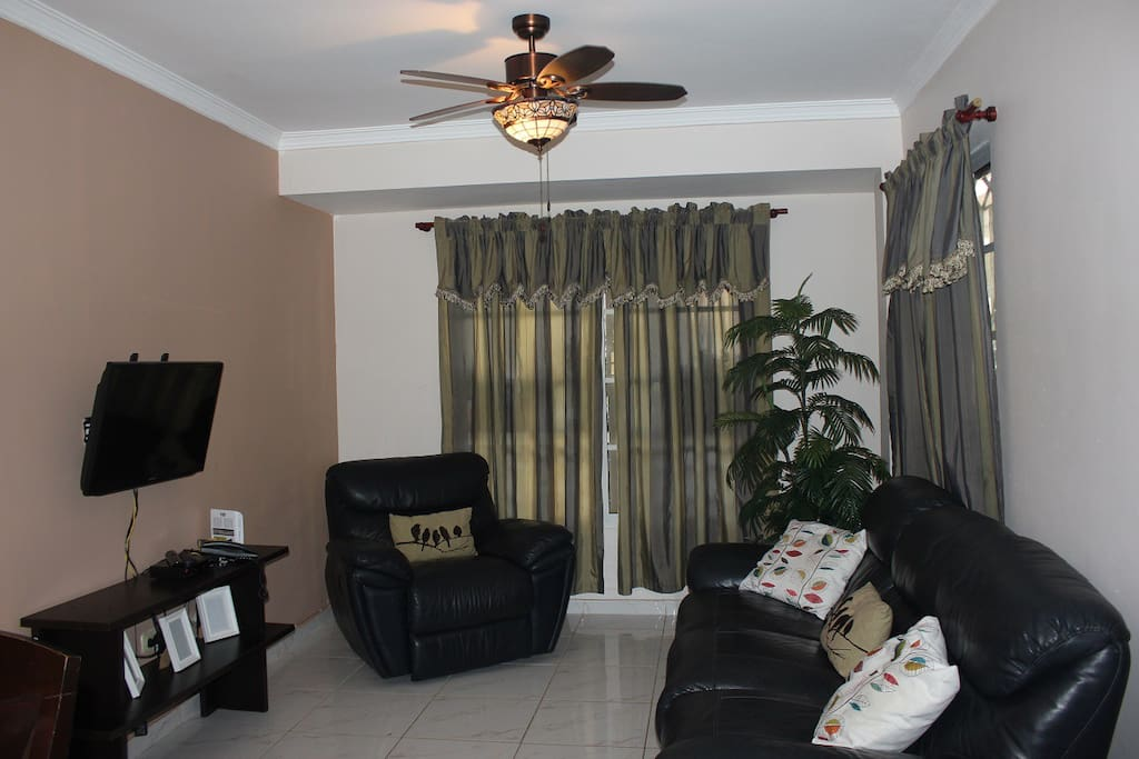 Living room with leather sofa and armchair, plus hd satellite smart tv