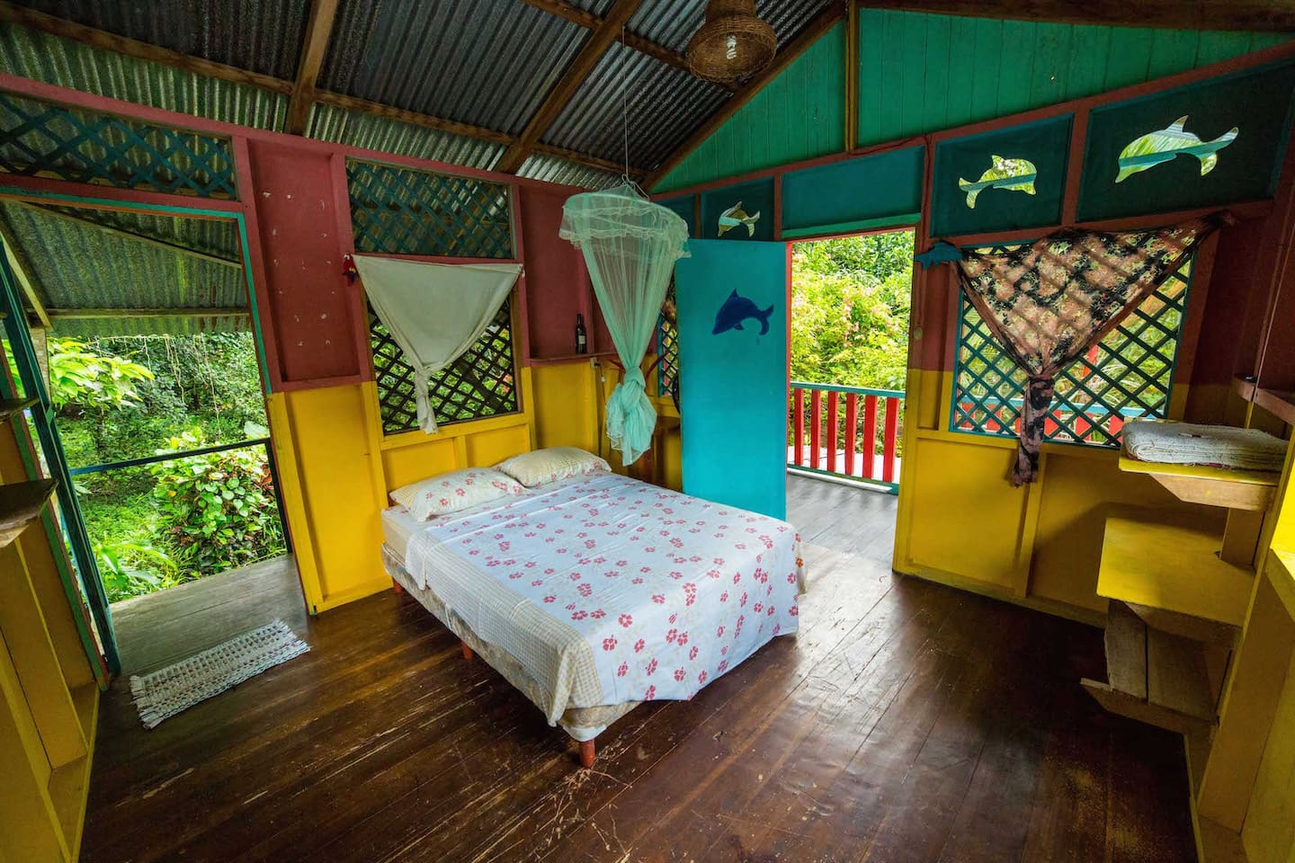 Bedroom with double bed, mosquito net & fan