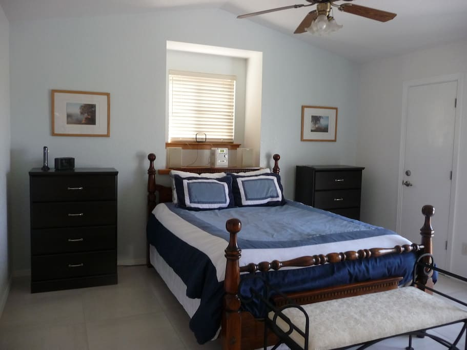 Master bedroom upstairs with queen bed and a door to the balcony