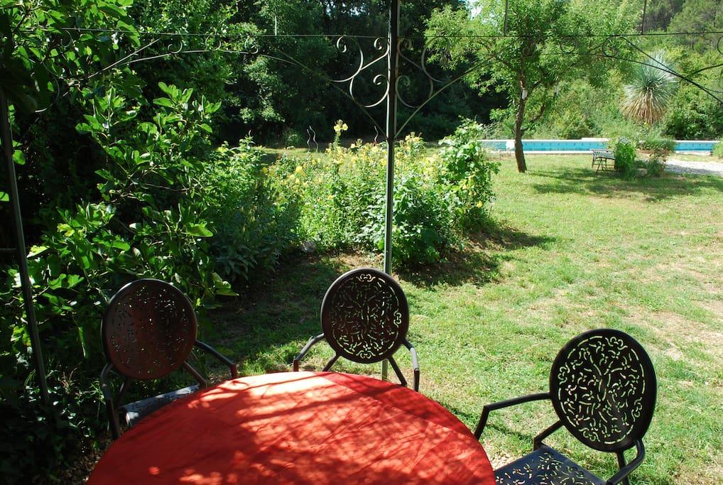 La tonnelle avec table et chaises à l'abri du soleil avec la piscine en vue, juste à la sortie de la maison dans un cadre de verdure préservé.