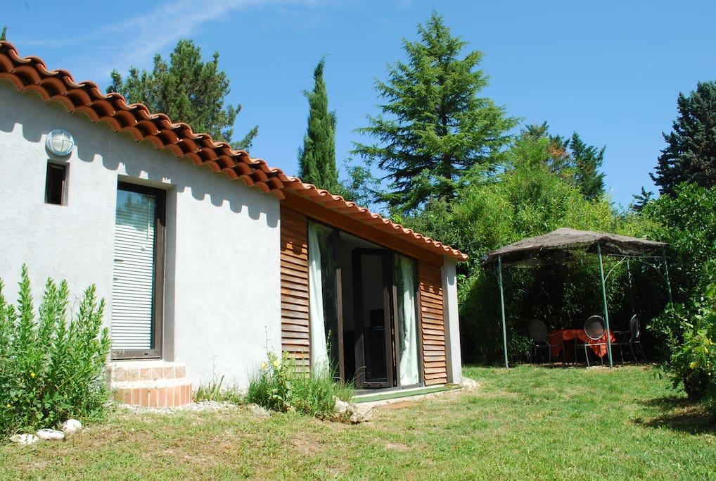 Vue extérieure avec baie vitrée en pente et petite porte donnant dans la salle d'eau, deux entrées indépendantes, très pratique quand on veut sortir dans le jardin.