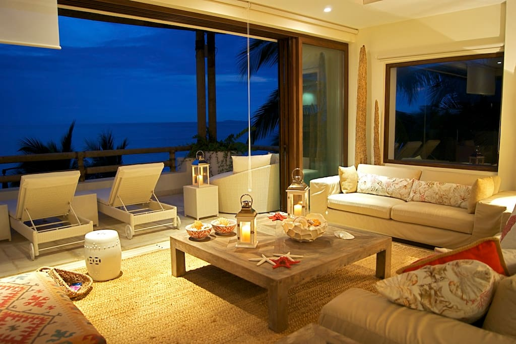 Main living room with outdoor terrace, at night. Windows open to the side integrating both areas. A breathtaking view!