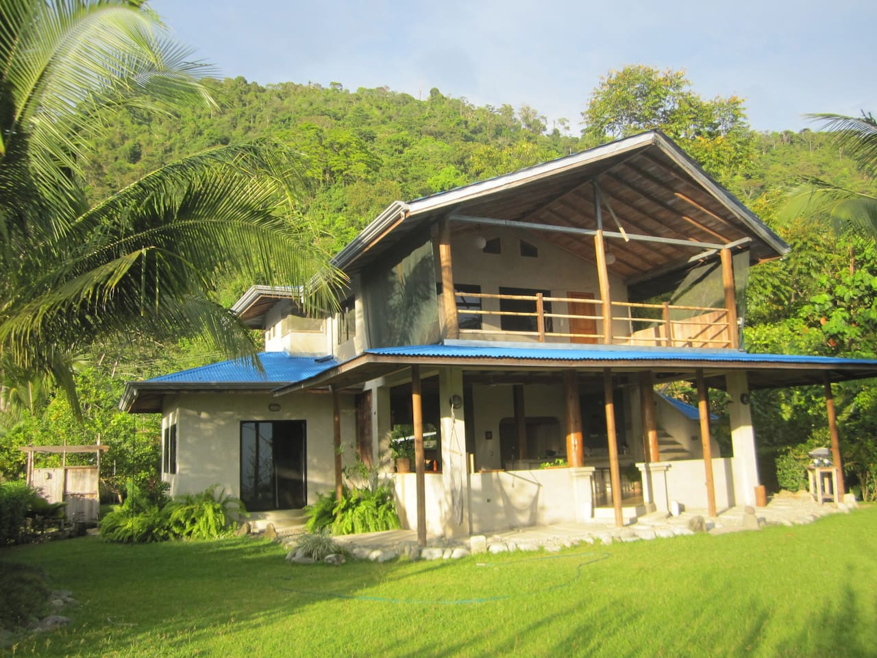 back of house faces ocean, sunset, and hovers over canopy of jungle