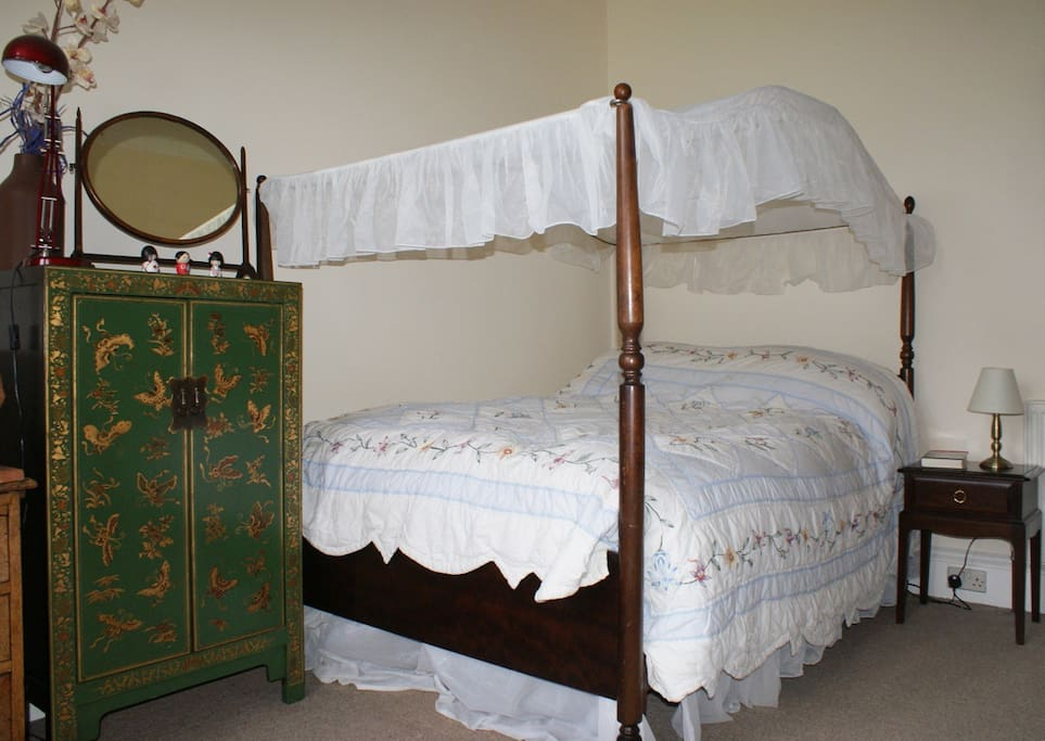 The master bedroom has a comfortable and romantic four-poster double-bed.