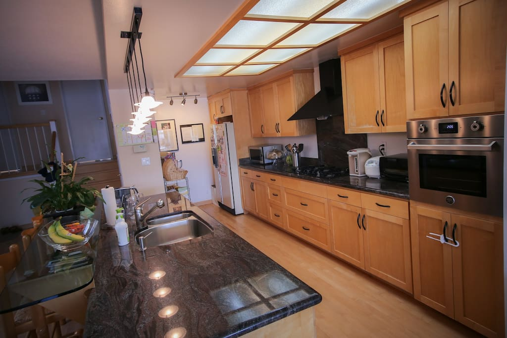 Gourmet kitchen with granite countertop, wine refrigerator, new convection oven, new dishwasher, and top-of-line cookware.