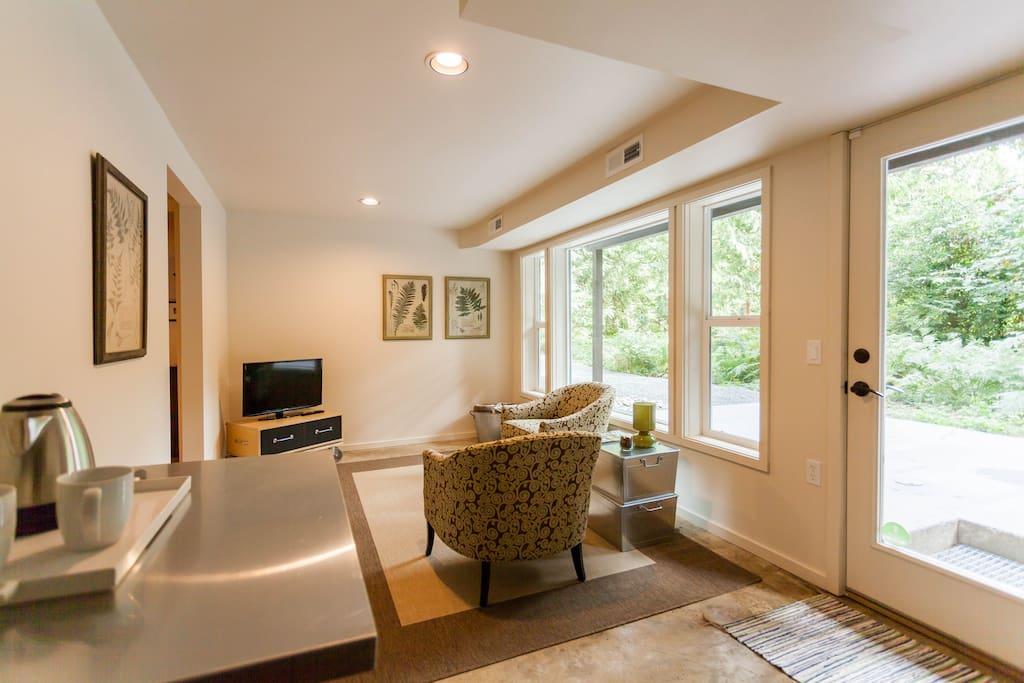 Sitting room with large windows overlooking terrace and fern garden.