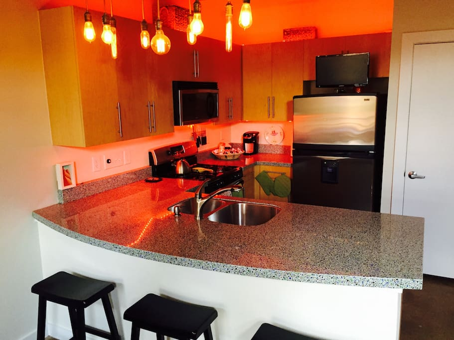 Kitchen has modern amenities: gas stove, micro, dishwasher, coffee maker, gorgeous recycled glass counter tops, dishes, utensils, and cook ware.