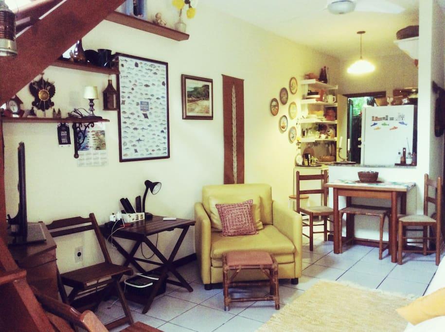 Sala ampla com sofá cama casal e sofá cama solteiro duas mesas Tv cozinha americana ar refrigerado ventilador de teto e banheiro
