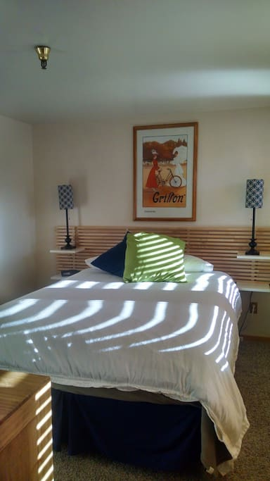 The sunlit bedroom has a queen-sized bed