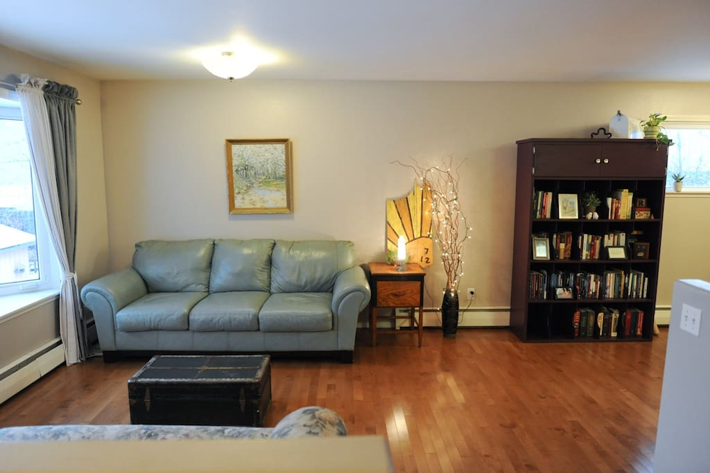 Living area: leather couch, hardwood floors, and a sense of peace welcomes you!
