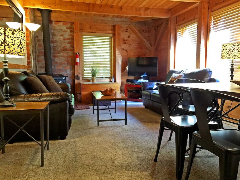 Right Unit: Cozy living room with flat screen TV, Blu-ray, soundbar with audio jack and wood burning stove.