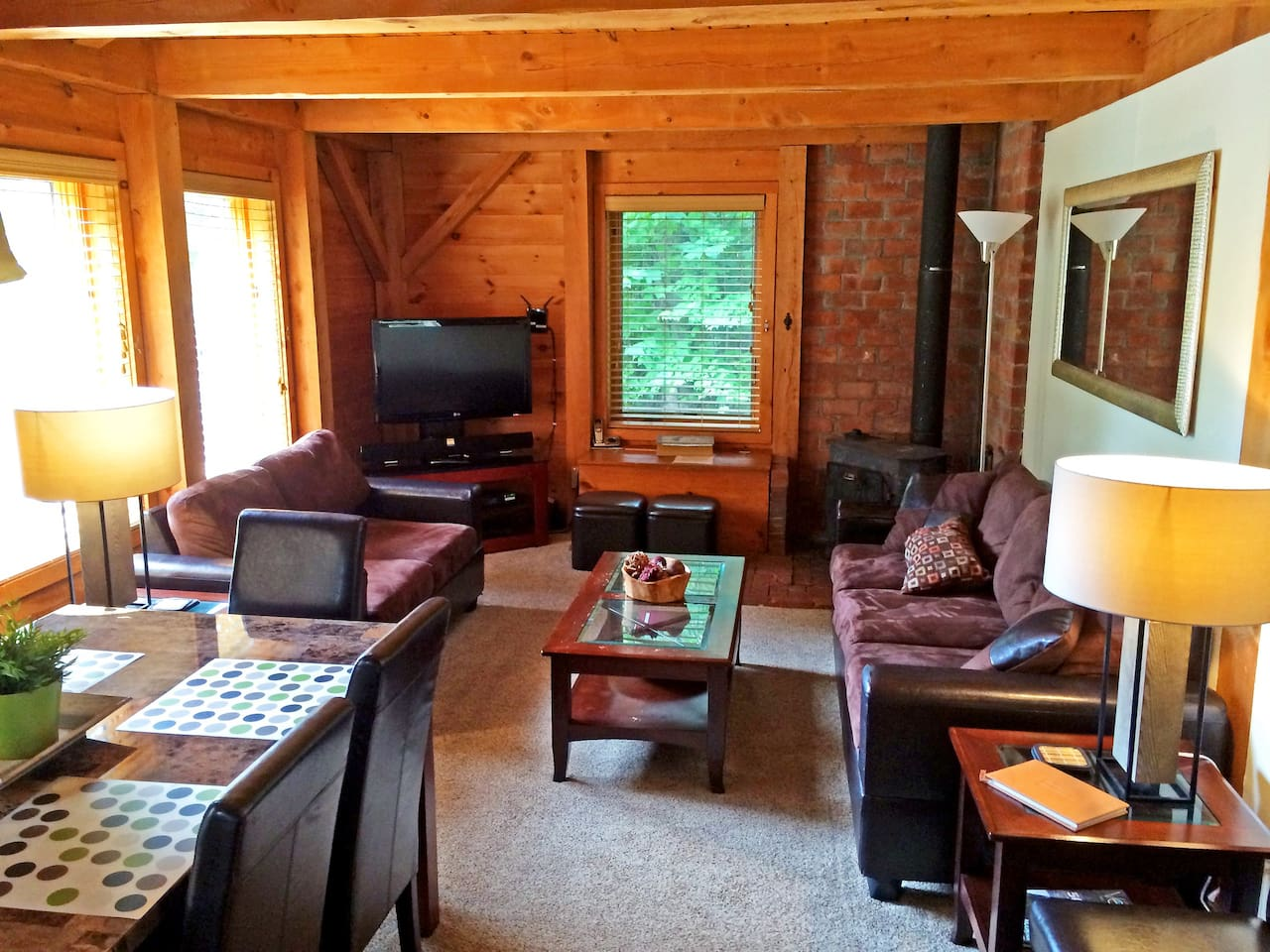 Living room with flat screen TV, WiFi, Apple TV, cable, BluRay, stereo and wood burning stove.