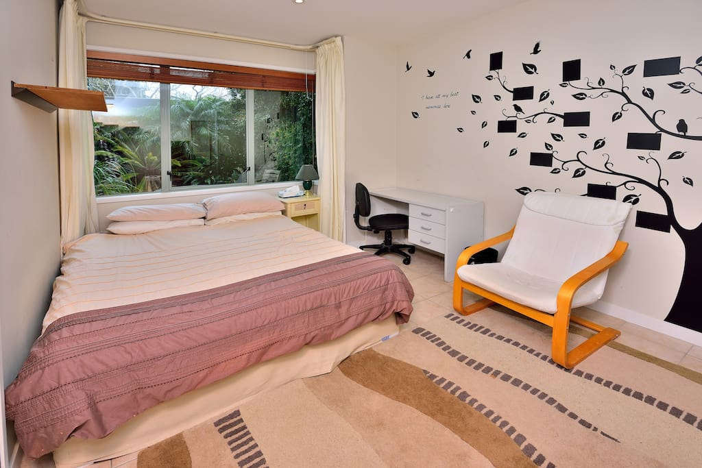 Your queen-sized bed, desk, easy chair, view into courtyard