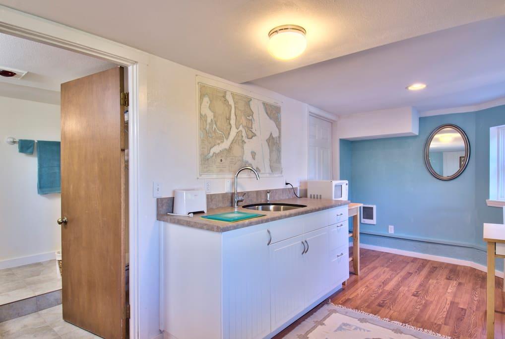 Kitchen sink, cabinets, and door to bathroom.  (Second door is to a storage area.)