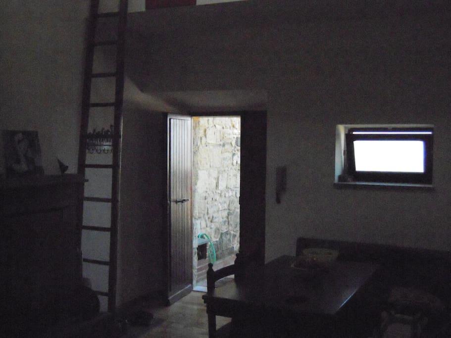 La cucina, il camino e la scala che sale al soppalco