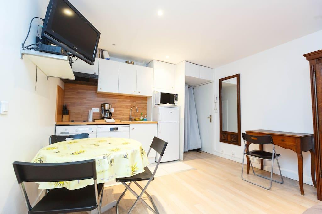 C'est une cuisine ouverte . Cette pièce est équipée avec : un réfrigérateur, un congélateur, un lave-vaisselle, des plaques à induction, une hotte aspirante, un micro ondes, un lave linge, un sèche linge, une cafetière, une bouilloire, un toaster,.