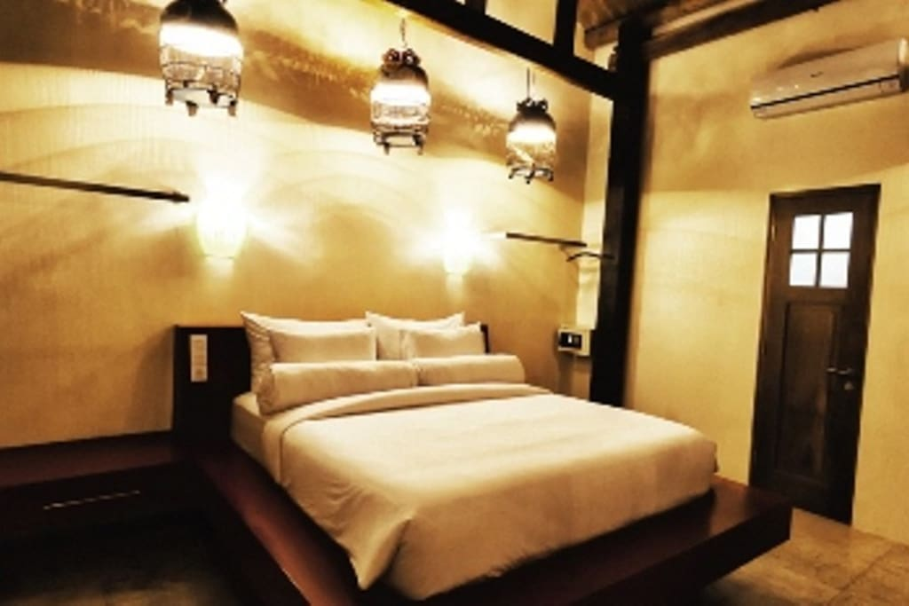 King sized bed with luxury cool and soft bamboo linen, re-purposed traditional bird cages light up the room.