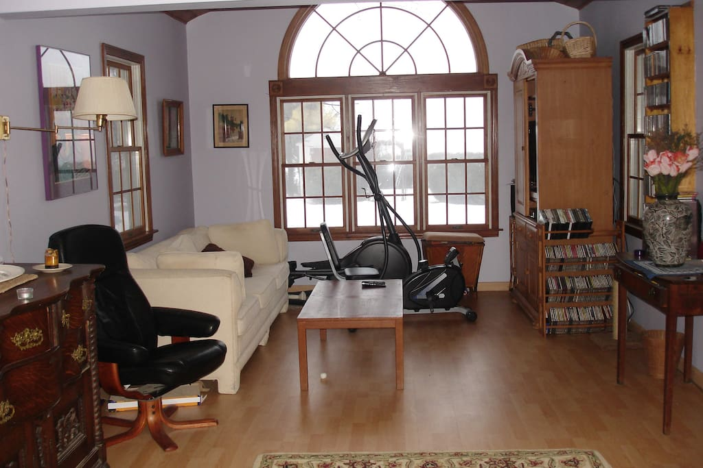 Family room with entertainment center, elliptical machine, and stationary bike with view out back