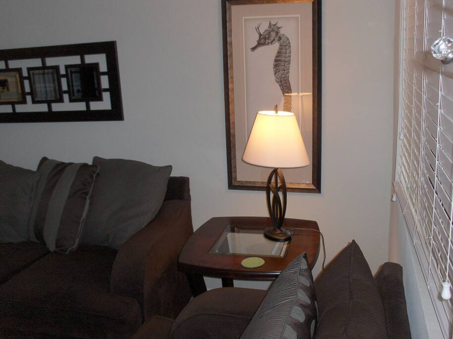 Corner end table separates the living room sofa and large chair with nice lighting for reading