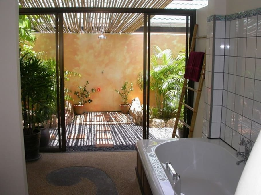 inside the huge bathroom with garden views and access to the rain shower to cool off