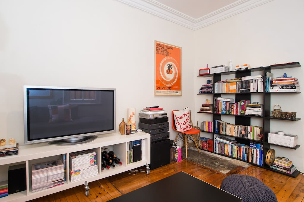 The living room with large TV and collection of books