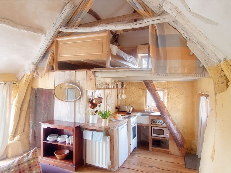 View of kitchen tucked under the ladder with crogloft and double bed above