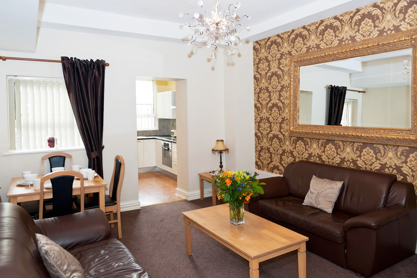 The sitting room has a sumptuous gold mirror and wallpaper.