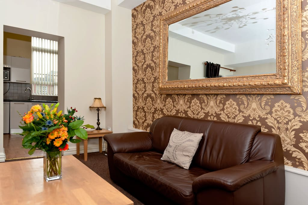 The antique gold mirror is perfectly offset by the wallpaper behind it.