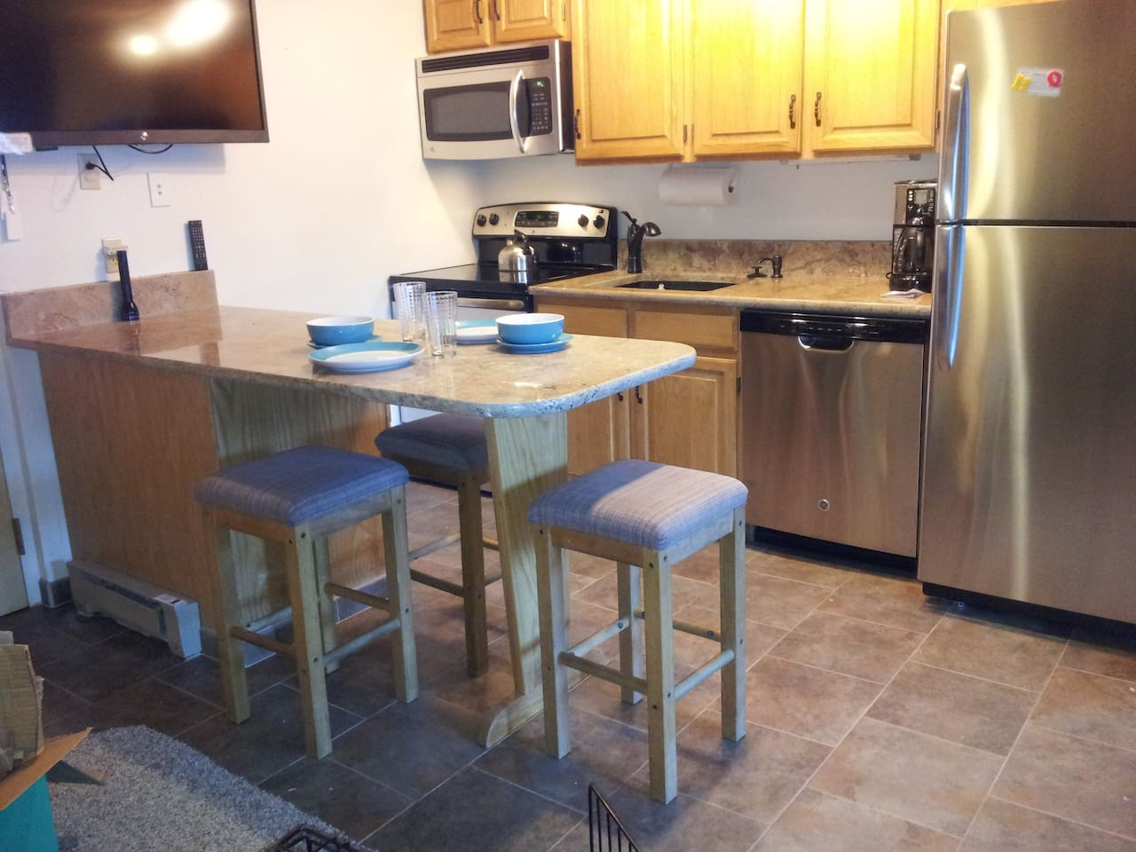 Full kitchen with granite counter tops and sink and stainlines steel appliances