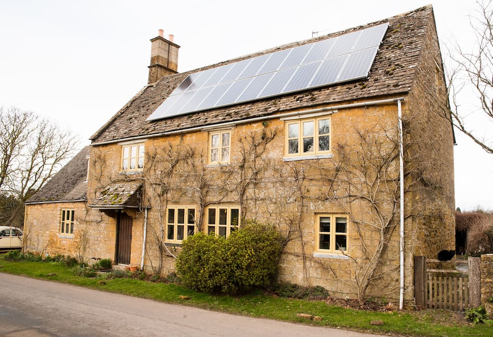 The front of the house in February. Currently we are the only house in the village with yellow windows and solar panels