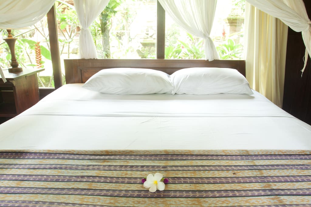 Your king sized bed with open view out to the garden and our family temple.