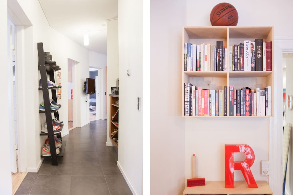 Hallway full of sneakers and living room full of books.