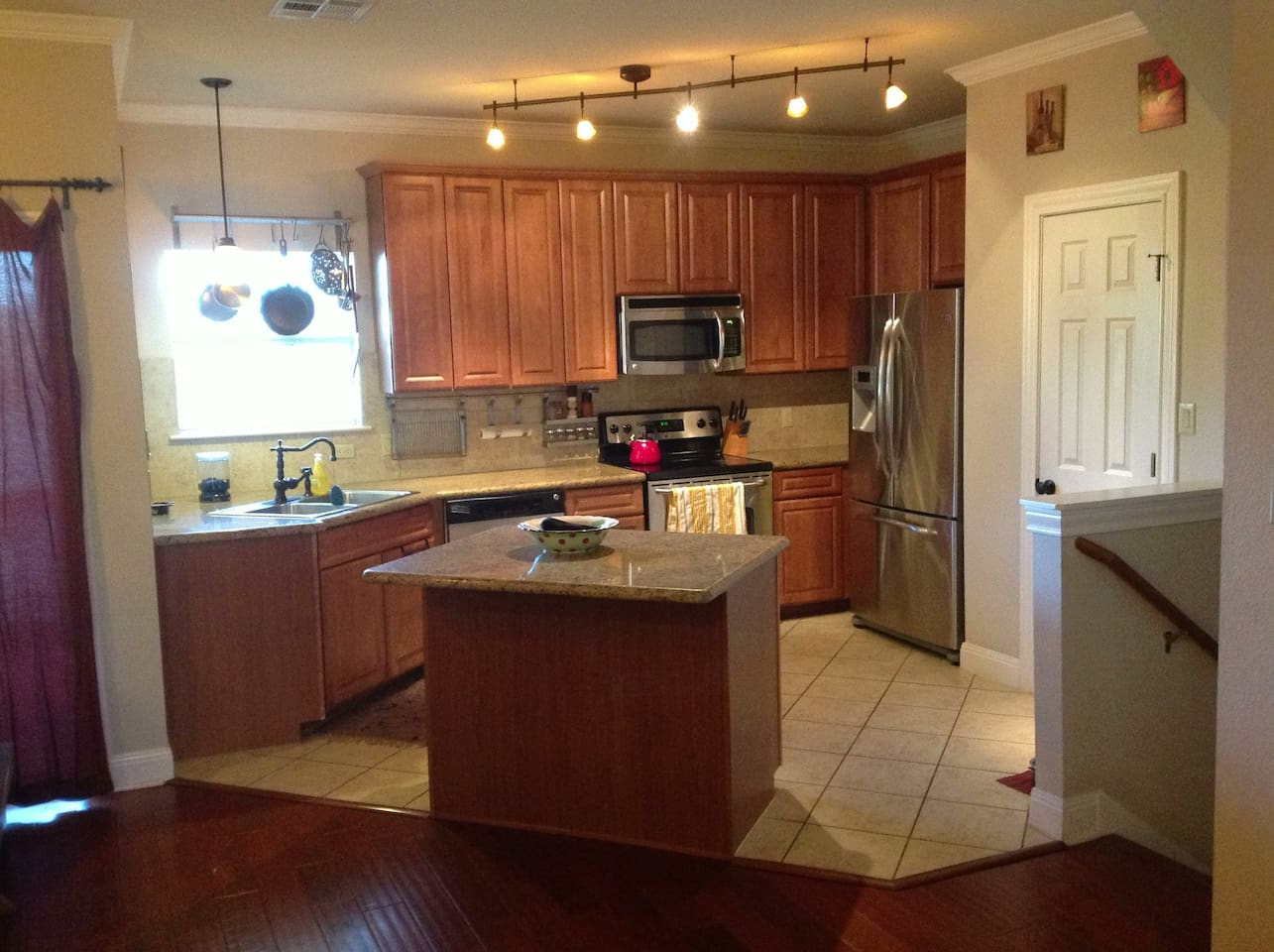 Kitchen with stainless steel appliances, tile flooring, granite counter tops, and track lighting.