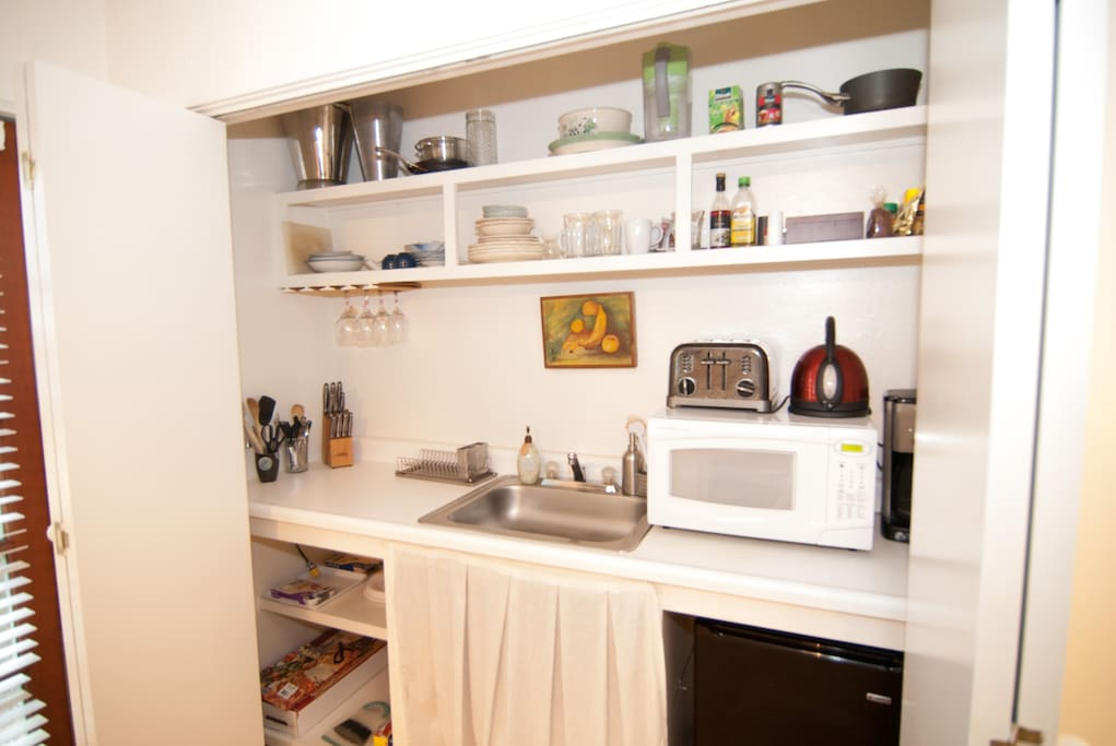 Fully stocked kitchenette with mini fridge, sink, microwave, coffee maker, and hot plates.