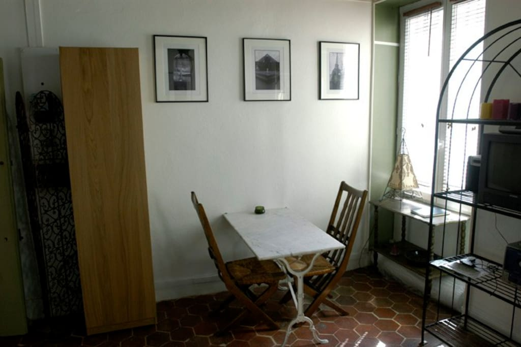 The authentic marble topped Paris bistro table in the main room of the studio. Original photography of Paris and other destinations decorate the walls of the apartment.