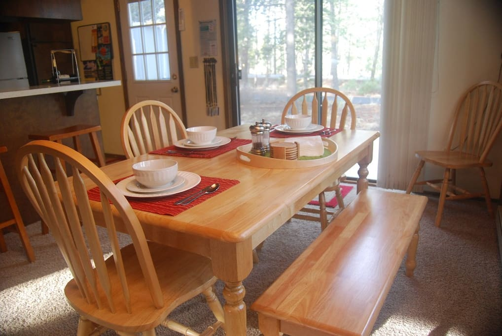 Dining table comfortably seats 6, with seating for 3 additional at nearby kitchen bar.