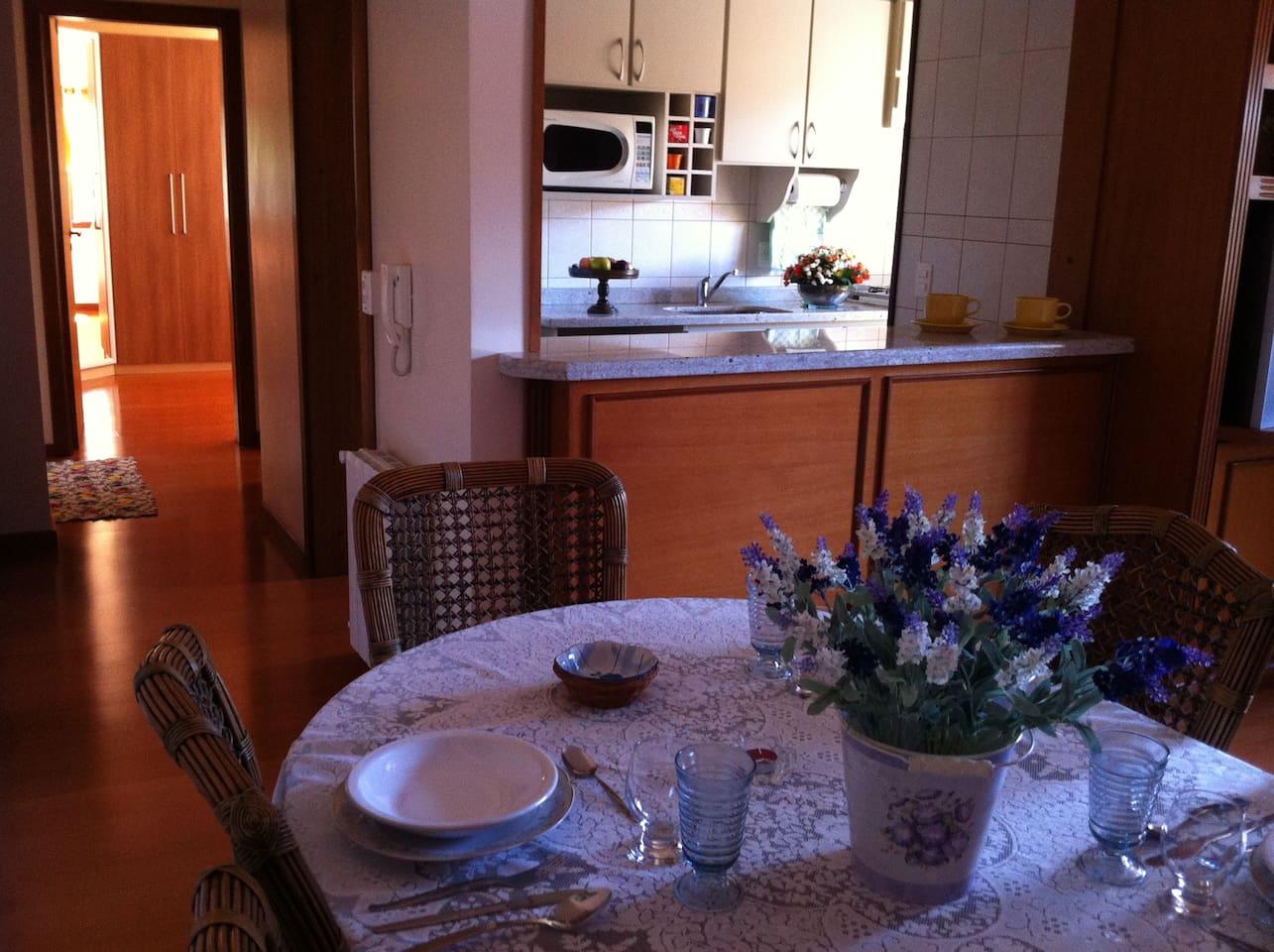Visão da Sala de Estar com mesa de jantar, cozinha americana com churrasqueira, geladeira, microondas, lavanderia e quarto de casal ao fundo.