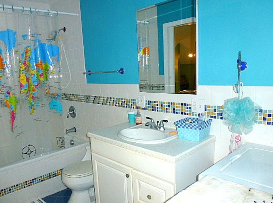 The bathroom is immaculately clean with shower, tub, and washer/dryer (right)