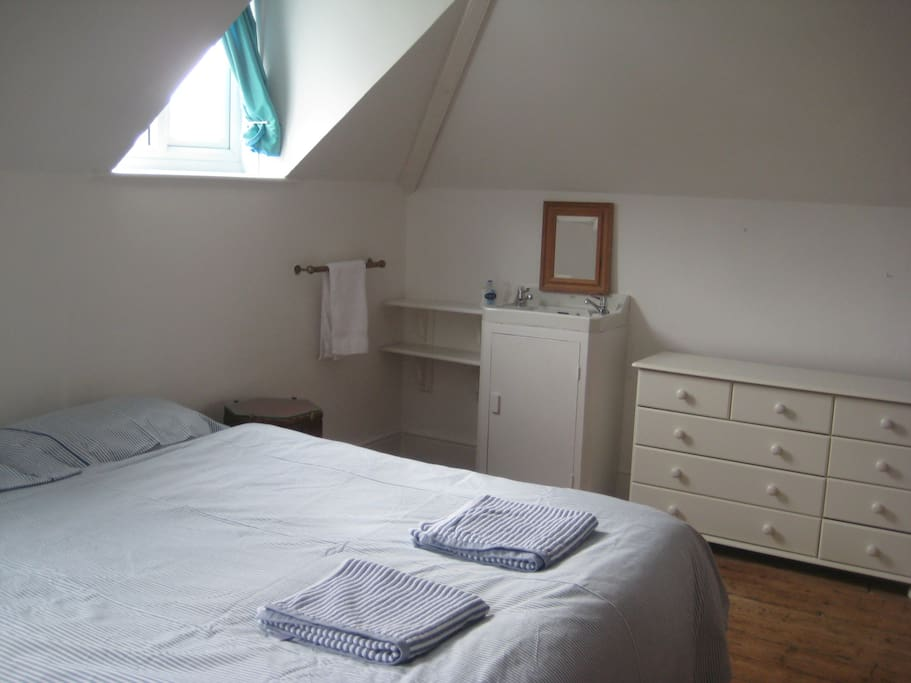Spacious double bedroom with view of sink.