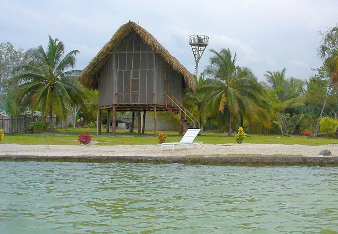 Private lagoon front Cabana on 9 Acres. Local woods, thatch roof and all screen front to catch the breeze.