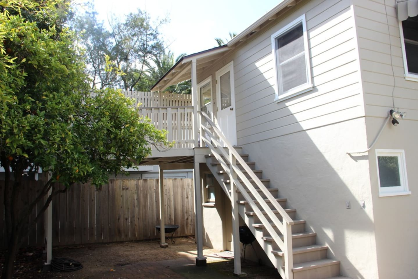 The apartment is located on the second story above the garage. There is a small deck off the entrance surrounded by a Loquat and Orange tree.